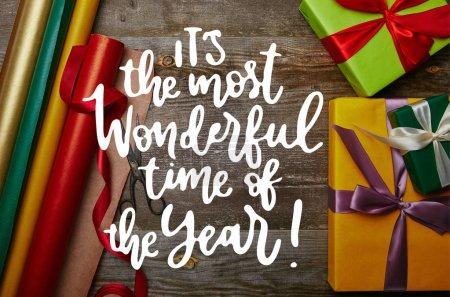 """Foto de Vista superior del arreglo de papeles de embalaje, año nuevo presenta con cintas y tijeras en tablero de madera de inspiración """"es la época más maravillosa del año"""" - Imagen libre de derechos"""