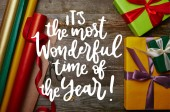 """top view of arrangement of wrapping papers, new year presents with ribbons and scissors on wooden tabletop with """"its the most wonderful time of year"""" inspiration"""
