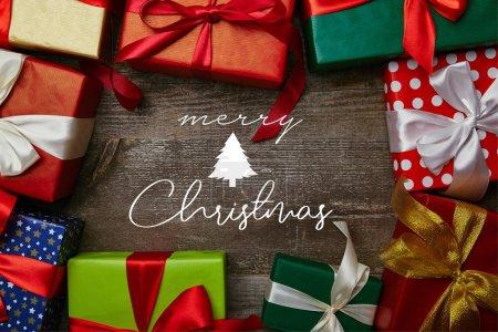 """Foto de Lay Flat con regalos envueltos en papeles de envolver diferentes con cintas en la superficie de madera con inscripción """"Feliz Navidad"""" - Imagen libre de derechos"""