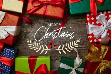"""Foto de Lay Flat con regalos de Navidad envueltos en papeles de envolver diferentes con cintas en la superficie de madera con inscripción """"Feliz Navidad"""" - Imagen libre de derechos"""
