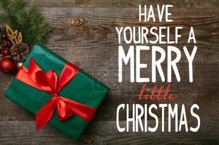"""Photo pour Vue du dessus du cadeau vert enveloppé avec ruban rouge et jouets de Noël sur fond en bois avec """"amusez-vous un joyeux petit Noël"""" inspiration - image libre de droit"""