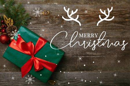 """Photo pour Vue du dessus du cadeau vert enveloppé avec ruban rouge et jouets de Noël sur fond en bois avec lettrage """"joyeux noël"""" - image libre de droit"""
