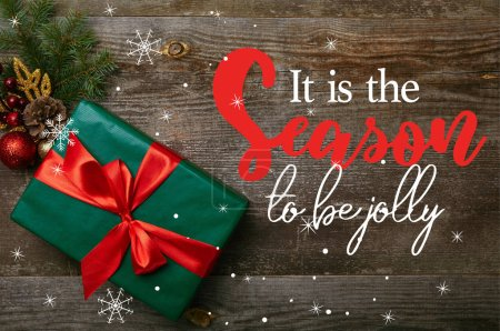"""top view of wrapped green present with red ribbon and christmas toys on wooden background with """"it is the season to be jolly"""" inspiration"""