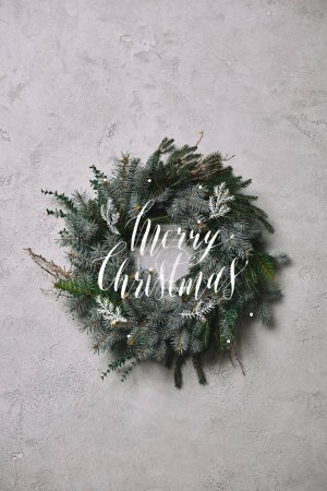 """fir wreath for Christmas decoration hanging on grey wall with """"merry christmas"""" lettering"""