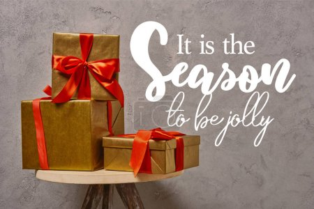 """golden Christmas gift boxes on chair near grey wall in room with """"it is the season to be jolly"""" inspiration"""