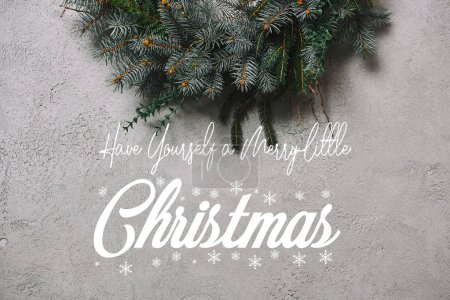 """cropped image of fir wreath for Christmas decoration hanging on grey wall with """"have yourself a merry little christmas"""" inspiration and snowflakes"""