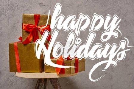 """Photo pour Coffrets cadeaux de Noël dorés sur chaise près du mur gris dans la chambre avec lettrage """"Joyeuses fêtes"""" - image libre de droit"""