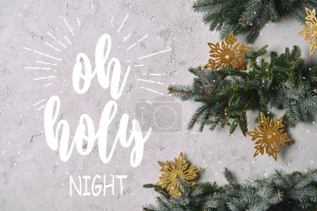 "cropped image of handmade Christmas tree with snowflakes hanging on grey wall with ""oh holy night"" lettering"