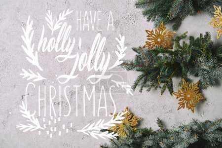 "cropped image of handmade Christmas tree with snowflakes hanging on grey wall with ""have a holly jolly christmas"" inspiration"