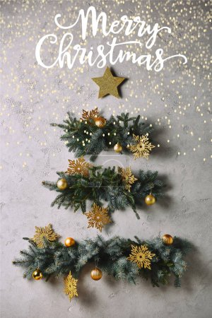 "handmade Christmas tree and star hanging on grey wall with ""merry christmas"" lettering and glowing lights"