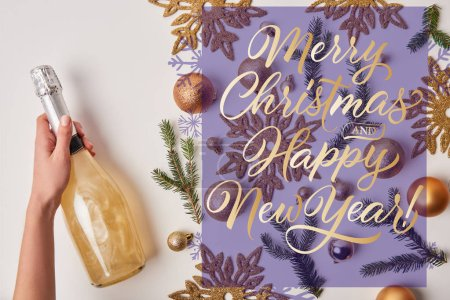 "cropped image of woman holding bottle of sparkling champagne near christmas decoration on white with ""merry christmas and happy new year"" lettering"