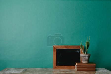 Cactus on books and wooden empty photo frame on green background