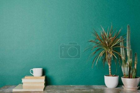Pflanzen in Blumentöpfen und Tasse Kaffee auf Büchern auf grünem Hintergrund
