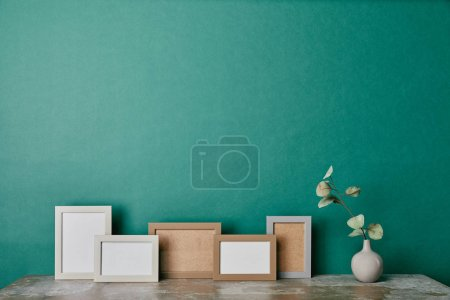 photo frames and vase with eucalyptus branch on table green background