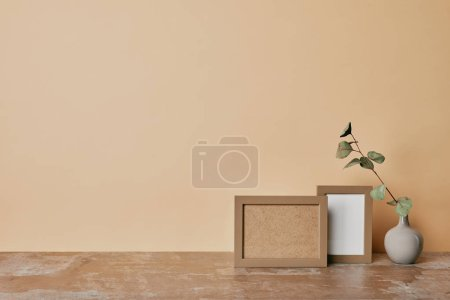 Two photo frames and vase with flower on table on beige background