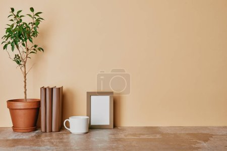 Plant, books, cup of coffee and empty photo frame on beige background