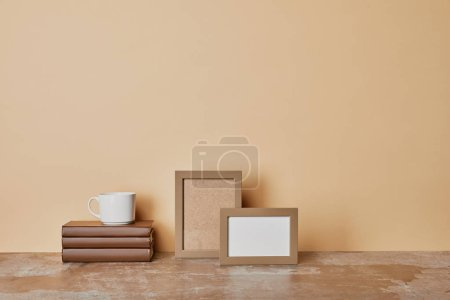 books, photo frames and cup  of coffee on beige background