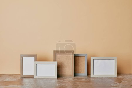 Various empty photo frames on dusty table on beige background