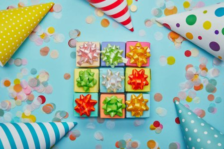 Top view of colorful gifts with bows, party hats and confetti on blue background