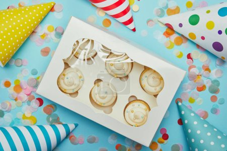 Top view of delicious cupcakes, party hats and confetti on blue background
