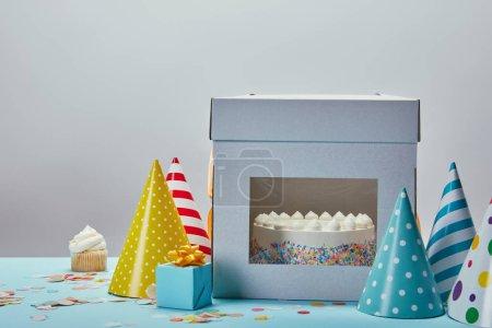 Geburtstagstorte, Partyhüte, Geschenk und Cupcake auf Tisch auf grauem Hintergrund