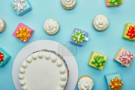 Top view of delicious cake, cupcakes and gifts on blue background