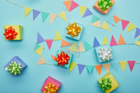 Top view of colofrul gifts and festive bunting on blue background