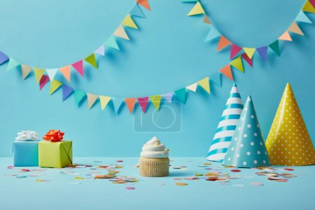 Tasty cupcake, party hats, confetti and gifts on blue background with colorful bunting