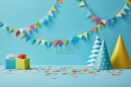 party hats, confetti and gifts on blue background with colorful bunting