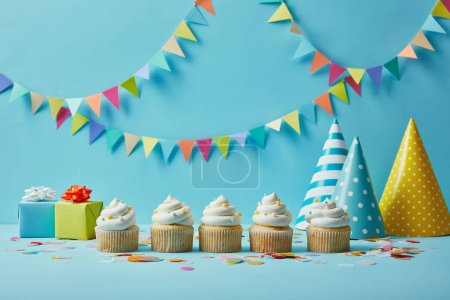 Delicious cupcakes with sugar sprinkles, party hats and gifts on blue background with colorful bunting