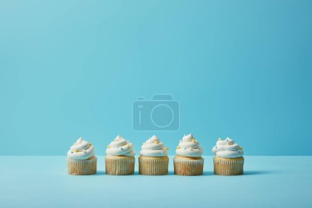 Delicious cupcakes with sugar sprinkles on blue background