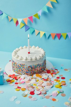 Tasty cake with sugar sprinkles and confetti on blue background with colorful bunting
