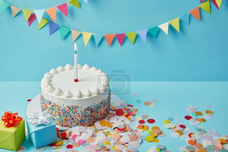 Photo for Delicious cake with sugar sprinkles, gifts and confetti on blue background with colorful bunting - Royalty Free Image
