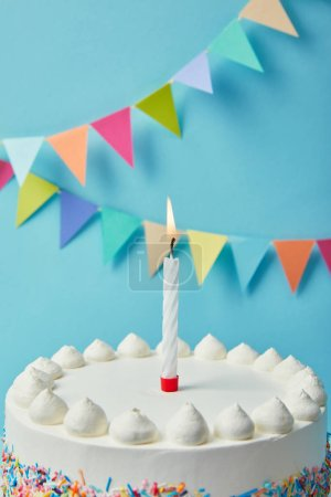 Candle on tasty birthday cake on blue background with bunting