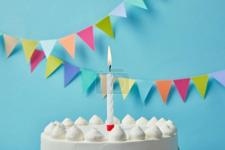 Candle on delicious birthday cake on blue background with bunting