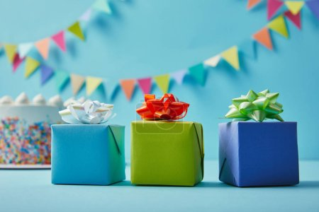 Gifts on blue background with colorful bunting