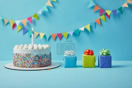 Tasty cake with sugar sprinkles and gifts on blue background with colorful bunting