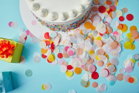 Top view of delicious cake, gifts and confetti on blue background