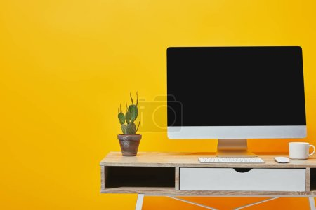 Cactus in flowerpot, white cup and computer at workplace on yellow