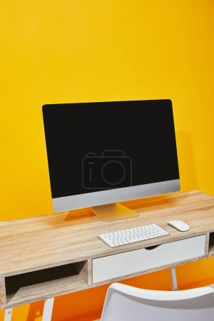 Computer at wooden table with chair near bright yellow wall