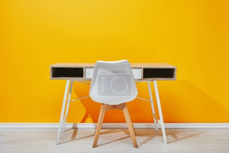 minimalistic wooden table with chair with yellow wall at background