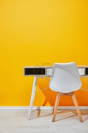 Wooden table with white chair naer yellow wall