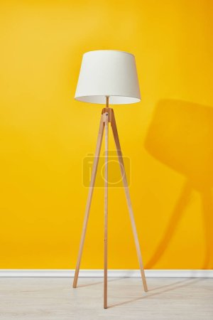 Photo for Minimalistic floor lamp near bright yellow wall - Royalty Free Image