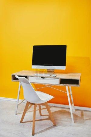 Computer mit leerem Bildschirm an Holztisch und Stuhl in der Nähe der gelben Wand