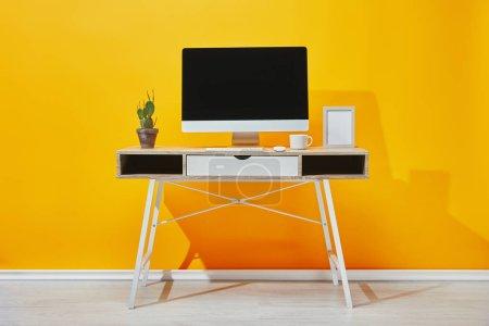 Photo pour Ordinateur, cadre photo, tasse de café et cactus sur le lieu de travail près du mur jaune - image libre de droit
