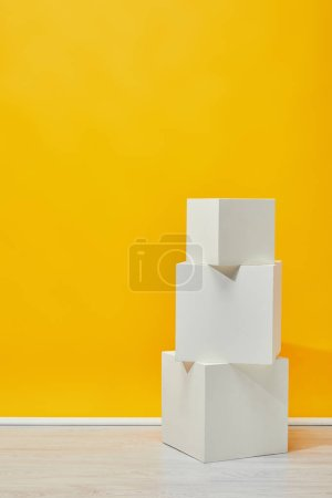 Photo for Minimalistic white plaster cubes arranged vertically near yellow wall - Royalty Free Image