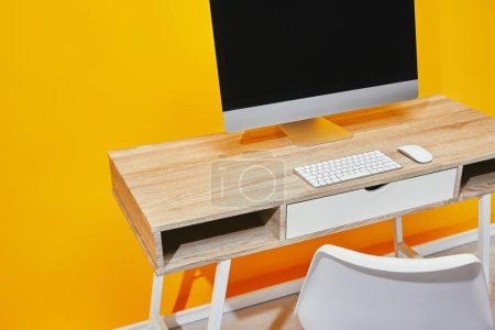 close up of workplace with computer and wooden table near yellow wall