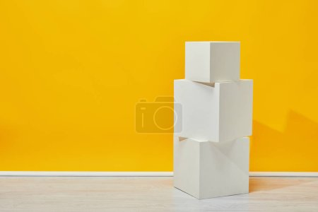 simple white plaster cubes arranged vertically near yellow wall