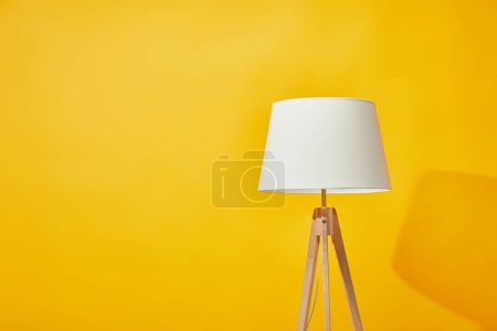 Minimalistic lamp on bright yellow background