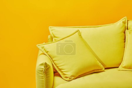 close up of bright sofa with pillows isolated on yellow